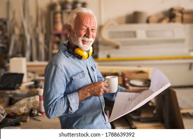 Waist up portrait of a likeable older carpenter. He is in a great mood, looking at the camera, winking and holding a coffee mug
