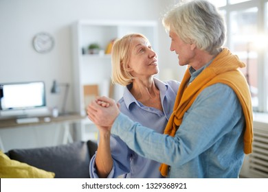 Waist up portrait of loving senior couple dancing at home, copy space