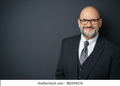 Waist Up Portrait of Mature Businessman with Facial Hair Wearing Suit and Eyeglasses Smiling Confidently at Camera and Standing in Studio with Dark Gray Background with Copy Space