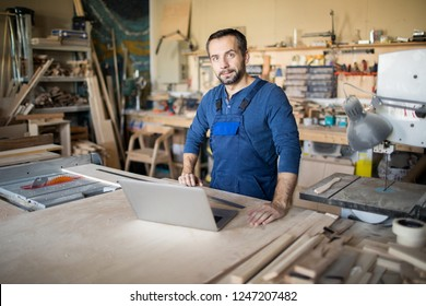 Waist up portrait of mature carpenter looking at camera and using laptop while working in joinery, copy space