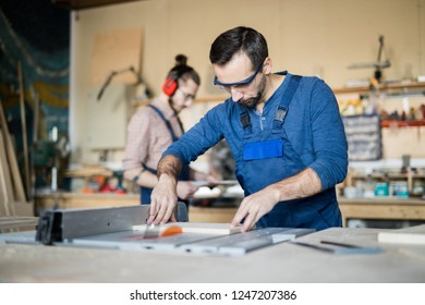 Waist up portrait of mature carpenter working with wood in joinery, copy space