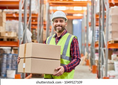 Waist up portrait of mature warehouse worker holding cardboard box smiling happily and looking at camera while doing shipping and deliveries, copy space
