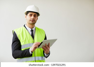 Waist up portrait of  Middle-Eastern engineer wearing hardhat posing against white background  holding tablet, copy space