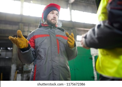 Waist up portrait of modern bearded worker  wearing warm jacket and hardhat discussing production with foreman  in workshop