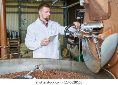 Waist up portrait of modern worker wearing lab coat using digital tablet while working in coffee production manufactory