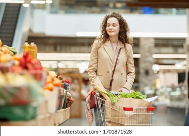 Waist up portrait of modern young woman pushing shopping cart while buying groceries in supermarket or farmers market, copy space