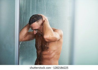 Waist up portrait of naked gentleman with hands behind his head standing under water drops