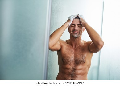 Waist up portrait of naked young gentleman with closed eyes enjoying water drops splashing on his body