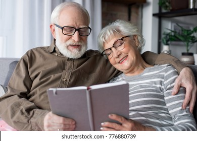 Waist up portrait of old married man and woman smiling with closed eyes. Husband is hugging wife while sitting at living room. Woman is holding photo album
