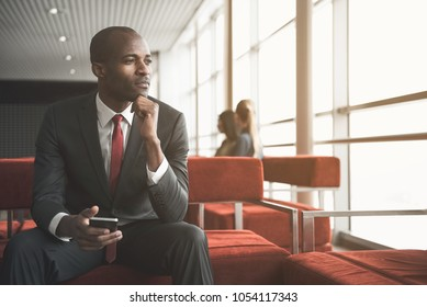 Waist up portrait of peaceful african male in suit sitting in lounge room with phone in hand, looking aside wistfully. People on background. Copy space in right side