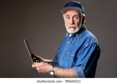 Waist up portrait of perplexed oldster holding notebook and looking at camera. Isolated on grey background