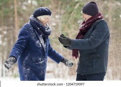 Waist up portrait  of playful senior couple enjoying snow in winter forest and laughing happily