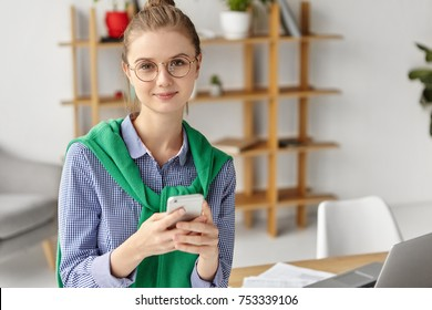 Waist up portrait of pleasant looking young female freelancer wears spectacles, shirt and green sweater, sits at working table, uses mobile phone for updating applications or checking newsfeed online