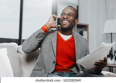 Waist up portrait of pleased guy holding documents while using mobile phone with joy. He is sitting inside