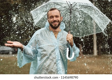 Waist up portrait of pleased male standing under umbrella with true delight. He is stretching hand feeling water drops on skin