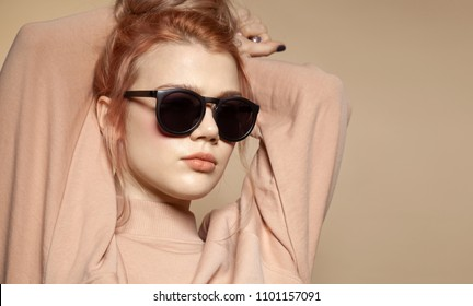 Waist up portrait of pretty fashionable girl in stylish sweatshirt. Sensual young female with nice foxy hair in dark glasses. Isolated on beige background