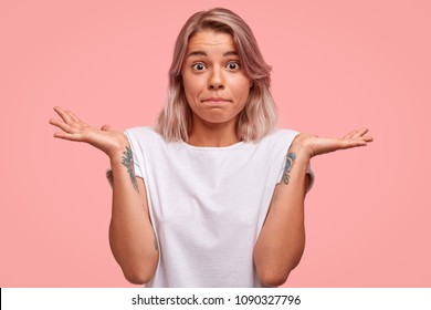 Waist up portrait of puzzled female with tattoo on arms, presses lips and shrugs hands with hesitation, wears casual white t shirt, being puzzled about something, isolated on pink background.