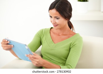 Waist up portrait of a relaxed lady looking at a tablet while sitting indoors - side view