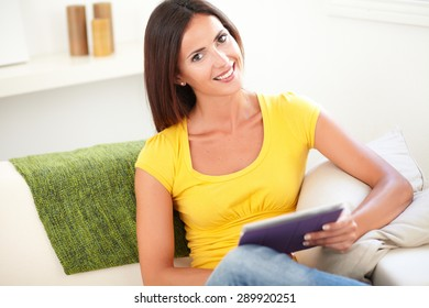 Waist up portrait of a relaxed young woman in yellow shirt holding a tablet while sitting indoors