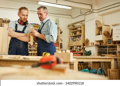 Waist up portrait of senior carpenter teaching apprentice  while working  in joinery workshop, copy space