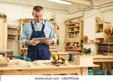 Waist up portrait of senior carpenter using tablet while working in joinery, copy space