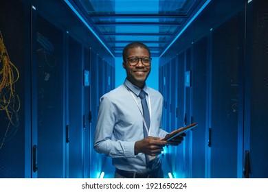 Sichern Sie das Porträt eines lächelnden afroamerikanischen Mannes, der bei der Arbeit mit einem Supercomputer im Rechenzentrum und beim Halten von Tablets an der Kabine steht, Kopienraum