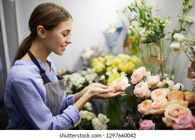 Waist up portrait of smiling female florist looking at flowers in glass display, copy space