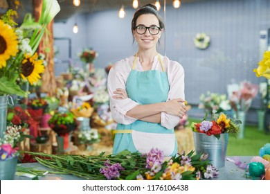 Waist up portrait of smiling female shopkeeper posing with arms crossed and looking at camera  in small flower shop, copy space