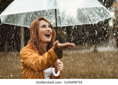 Waist up portrait of smiling girl standing outdoors with umbrella in hands. She is stretching hand and opening mouth in true pleasure