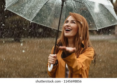 Waist up portrait of smiling pretty female enjoying rainy weather. She is standing under umbrella and stretching hand catching water drops with content