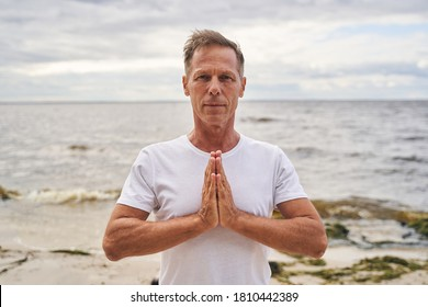 Waist up portrait of sporty male standing on sea shore and holding hands in namaste position