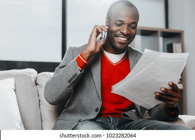 Waist up portrait of stylish african man relaxing on sofa. He is looking at records with smile and talking by cellphone