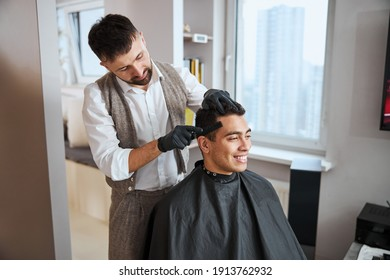 Waist up portrait of stylishly dressed barber prepares the handsome Indian client for a haircut