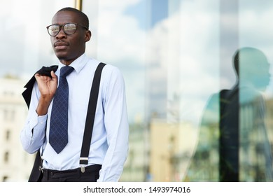 Waist up portrait of successful African-American businessman posing outdoors standing by glass window and holding jacket casually, copy space