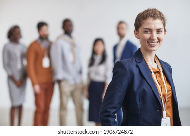 Waist up portrait of successful businesswoman smiling at camera while standing with multi-ethnic team in background, copy space