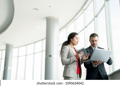 Waist up portrait of successful modern businesswoman talking to partner in office and using laptop standing by window, copy space
