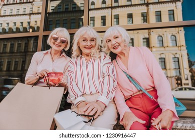 Waist up portrait of three adult beautiful women spending free time together while holding shopping bags