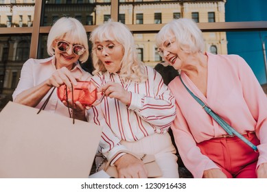 Waist up portrait of three adult ladies sitting and discussing about new fashion clutch