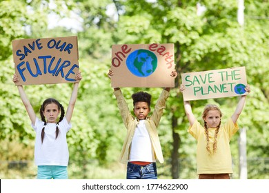 Waist up portrait of three children holding signs with SAVE PLANET SAVE FUTURE while protesting for nature outdoors, copy space