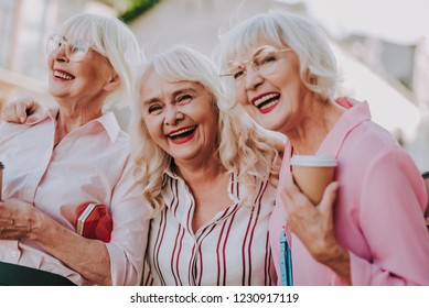 Waist up portrait of three positive older women joking and having fun together