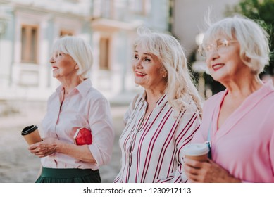 Waist up portrait of three stylish grandmothers are walking on street and smiling