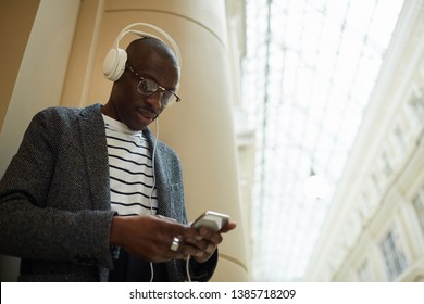 Waist up portrait of trendy African man wearing headphones and using smartphone in architectural building, copy space