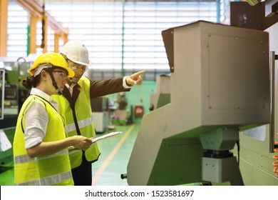 Waist up portrait of two Asian factory workers with safety helmet check implement result at monitor of industrial machine. Manufacturing industry to produce car spare parts. Quality assurance (QA).