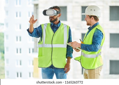 Waist up portrait of two modern construction workers using VR gear to visualize projects  on site, copy space