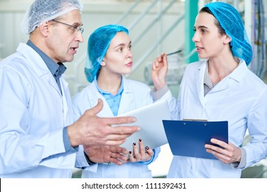 Waist up portrait of two young women asking questions to senior factory worker during training seminar for new specialists standing in clean workshop of modern plant.