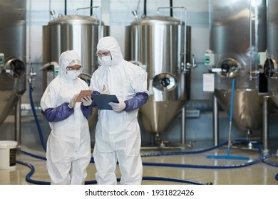 Waist up portrait of two young workers wearing hazmat suits while using digital tablet at modern chemical factory, copy space