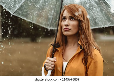 Waist up portrait of unhappy woman standing outside and holding umbrella. She is looking at water drops with dissatisfaction