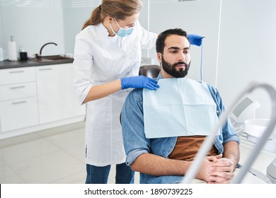 Waist up portrait view of the doctor putting a protective towel on her multiracial male patient sitting at the dentist armchair before the procedures. People, medicine, stomatology and health care
