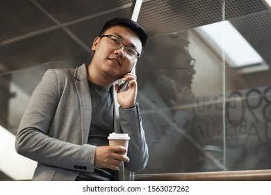 Waist up portrait of young Asian businessman speaking by phone while standing by glass wall in modern office interior, copy space
