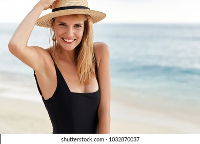 Waist up portrait of young cute female traveler in bikini and hat discovers tropical country, poses on ocean coastline, happy to spend summer holidays abroad, has positive lovely expression.